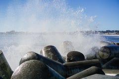 Vågor som bryter på de konkreta kvarteren som skyddar bryggan av Santa Cruz Harbor, Kalifornien Arkivbild