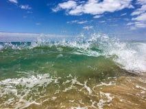 Vågor som bryter på en sandig strand arkivbilder