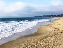Vågor som bryter på en sandig strand royaltyfria bilder