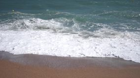 Vågor som bryter på en sandig strand stock video