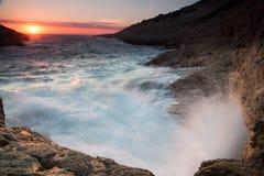 Vågor som bryter på en stenig kust på solnedgången Royaltyfria Foton