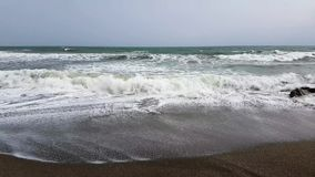 Vågor som bryter på en stenig strand lager videofilmer