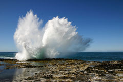 Vågor som bryter på en vagga på kusten Royaltyfri Bild