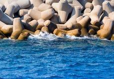 Vågor som bryter på stora konkreta tetrapods - blått hav arkivbild
