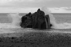 Vågor som bryter på, vaggar på stenkustlinjen arkivfoto