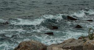 Vågor som bryter på, vaggar, Tarragona royaltyfri bild