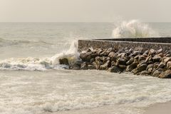 Vågor som bryter på, vaggar väggen arkivfoto