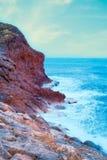 Vågor som bryter till och med den steniga kusten royaltyfri foto