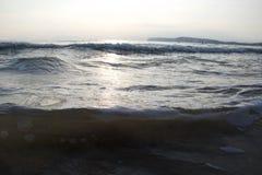 Vågor som bubblar försiktigt; större vågor som bryter i distnace royaltyfria bilder