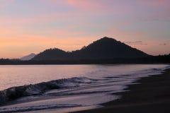 Vågor som kommer med den målade soluppgången Arkivfoton