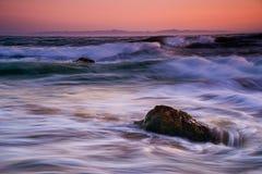 Vågor som kraschar över en vagga på solnedgången Royaltyfria Bilder