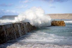 Vågor som kraschar över havsväggen Arkivbild