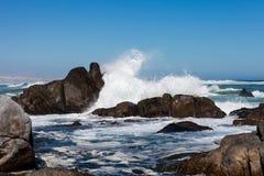 Vågor som kraschar mot stenblock Arkivbild