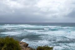 Vågor som kraschar på den steniga kustlinjen med illavarslande moln för mörker arkivfoton
