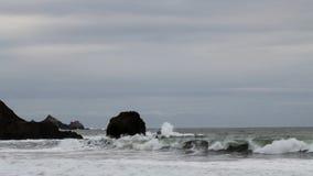 Vågor som kraschar på kust, vaggar med mulen himmel stock video