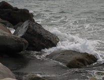 Vågor som kraschar på, vaggar på den svarta sandstranden Arkivbild