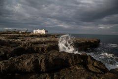 Vågor som kraschar på, vaggar i Apulia Arkivbilder