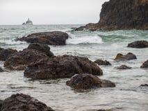 Vågor som kraschar på, vaggar med den Tillamook fyren Fotografering för Bildbyråer