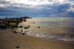 Vågor som kraschar på, vaggar och stranden Arkivfoton