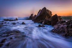 Vågor som kraschar på, vaggar på solnedgången, i Corona del Mar Royaltyfria Foton