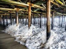Vågor som kraschar pelarna under Santa Monica Pier - Santa Monica, Los Angeles, LA, Kalifornien, CA Arkivbilder