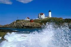 Vågor som kraschar runt om Nubblefyren i Maine Arkivfoto