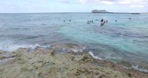 Vågor som plaskar en vagga och simmar turister i avståndet, Bermuda öar, norr Atlantic Ocean lager videofilmer