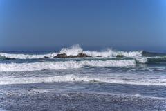Vågor som plaskar på enormt, vaggar, av kust, arkivfoto