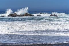 Vågor som plaskar på enormt, vaggar, av kust, royaltyfria foton