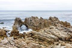Vågor som plaskar på enormt, vaggar, längs en stenig strand royaltyfri fotografi