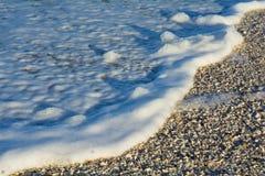 Vågor som rullar över massor av skal Arkivfoto