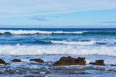 Vågor som rullar till, vaggar, skummande färgstänk, Victoria, Australien Arkivfoto