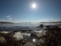 Vågor som slår den steniga kusten med den ljusa solen och det snöig berget Arkivbilder
