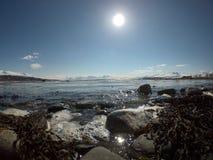 Vågor som slår den steniga kusten med den ljusa solen och det snöig berget Arkivbild