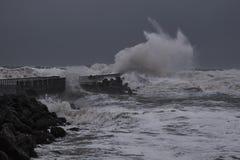 vågor som slår mot pir under storm i Nr Vorupoer på Nordsjönkusten Arkivbild