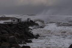 vågor som slår mot pir under storm på Nordsjönkusten i Danmark Arkivbilder