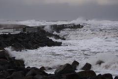 Vågor som slår mot pir under stormen i Nr Vorupør på Nordsjönkusten Arkivbilder