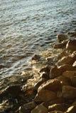 Vågor som sveper på den steniga kusten Arkivbilder