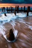 Vågor virvlar runt runt om pirpilings i den Delaware fjärden på solnedgång, s Fotografering för Bildbyråer