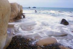 Vågorna och den steniga stranden Arkivfoto