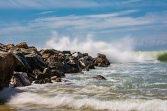 Vågorna som bryter på en stenig strand som bildar en stor sprej royaltyfria foton