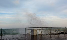 Vågorna som bryter på förtöja som bildar en sprej Vågor bryter havsinvallningen i storm arkivbilder
