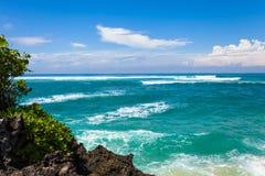 Vågorna som bryter på, vaggar och att bilda en sprej arkivfoton