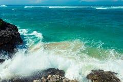 Vågorna som bryter på, vaggar och att bilda en sprej royaltyfri fotografi