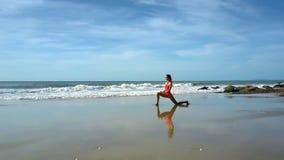 Vågrulle på stranden till flickan i yoga poserar på sand arkivfilmer
