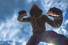 Våldsam attack, oigenkännligt manligt sparka för brottsling och punchin royaltyfria foton