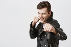 Våldsam och säker ung stilig man i svarta hållande nävar för läderomslag som är främsta av honom som, om klart för kamp eller Arkivfoton