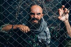 Våldsam terrorist med kniven mot metallraster royaltyfria foton