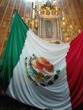 Vår dam av Guadalupe och den mexikanska flaggan arkivbild