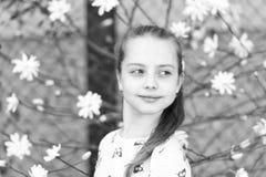 Vår-, easter och ferieberömbegrepp Liten flicka på den blom- blomningen i vår Barn med att blomstra blommor arkivbild